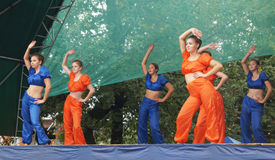 Young girls in bright suit dance and show acrobatic stunts on sc Royalty Free Stock Photos