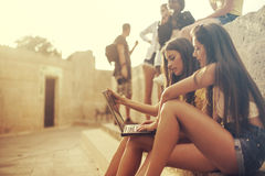 Young girls browsing on the internet. Two girls using a laptop on the street Royalty Free Stock Photos