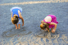 Young Girls Burying Feet in Sand. Two young girls burying their feet in sand, drawing heart shapes in sand gravel Stock Photography
