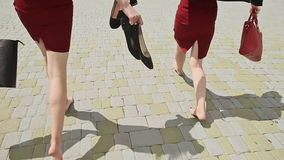 Young girls businesswoman running with a barefoot pleasure, having finished the working day. Holding shoes and bags stock footage