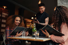 Young girls at cafe giving order to the waiter. Young women seated at a table holding menus in a restaurant. Young girls at cafe making  choice and place their Royalty Free Stock Photography