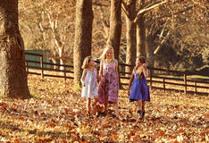 Young girls children kids playing running in fallen autumn leave Royalty Free Stock Images