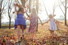 Young girls children kids playing running in fallen autumn leave. S royalty free stock image
