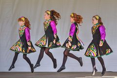 Young girls in colorful costumes performing an Irish dance stock image