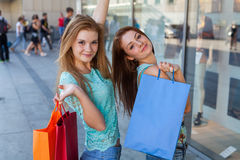 Young girls with colorful shopping bags. Season of sales. Royalty Free Stock Photography