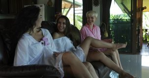 Young girls coming indoors talking sit on couch in living room, beautiful women friends communication stock footage
