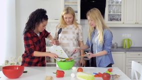 Young girls cooks salad and mix fresh cutting vegetables in a bowl. Three young girlfriends spend their leisure time together and cooking a fresh salad at the stock video footage