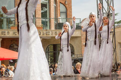 Young girls dancers in traditional Georgian white dresses dancing on stage Royalty Free Stock Image