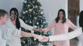Young girls dancing near the Christmas tree stock footage
