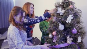 Young girls decorate Christmas tree stock video footage