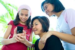 Young girls of different ages looking at a cell ph Royalty Free Stock Photography