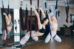 Young girls do aerial yoga in the gym Royalty Free Stock Photos