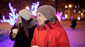Young girls drink coffee in the winter in the center of the city, near the winter decorations. Christmas, new year stock video