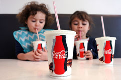 Young girls drinking Coca Cola. Two young girls Talya and Naomi Ben-Ari age 07- 03 drinking Coca Cola. Sugary drinks are a major contributor to health conditions royalty free stock photos