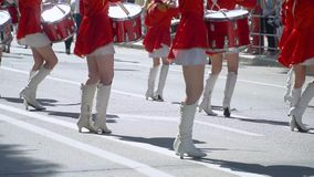 Street performance of festive march of drummers girls in red costumes on city street. Slow motion. Young girls drummer in red at the parade. Street performance stock video footage
