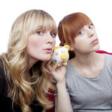 Young girls ears on piggybank Stock Image