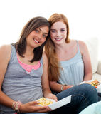 Young girls eating burgers and fries. On the sofa Stock Photos