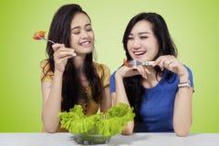 Young girls eating salad Royalty Free Stock Photos