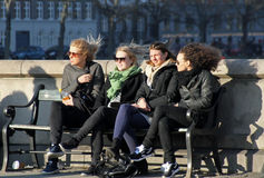 Young girls enjoy the sun in Copenhagen. Young girls sit on bench in Copenhagen, and enjouy the sunshine Stock Image
