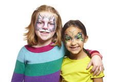 Young girls with face painting of cat and butterfly. Smiling on white background stock photography
