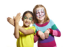 Young girls with face painting of cat and butterfly royalty free stock image