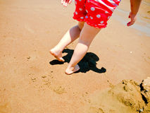 Young girls feet and legs walking on the beach. The lower body of a young girl walking on the sand of a beach Royalty Free Stock Photos
