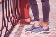 Young girls foot in jeans and sneakers sports shoes walking on road. Near metal fence. Leisure and lifestyle Stock Photography