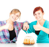 Young girls friends with cake and thumbs up Royalty Free Stock Images