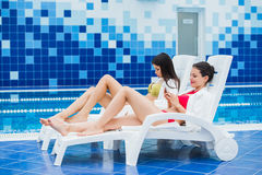 Young girls friends messaging with friend on her smartphone. Relaxation spa and technology social networks concept. royalty free stock photos