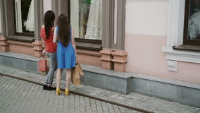 Young girls friends standing near shop window with wedding dresses and discuss. slow mo stock footage