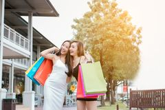 Young girls friends on the street outdoors at outlet mall laughing and smiling with shopping bags. royalty free stock photography