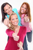 Young girls gesturing thumb up sign. Three young girls gesturing thumb up sign Stock Photos