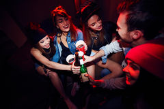 Young Girls Getting Drunk at Party. High angle of several young people, girls and one man, getting drunk at club party, sitting close together in dark red lit Royalty Free Stock Photography