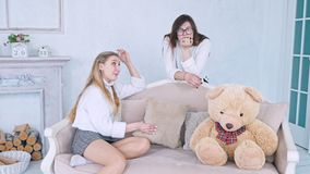 Young girls girlfriends are fighting with pillows and a teddy bear in a photo shoot. Slow motion stock video footage
