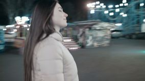 Young girls go to the merry-go-round. Two young girls are walking along the amusement park to the cashier stock footage