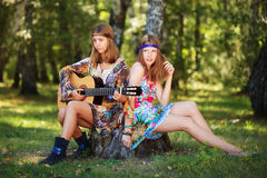 Young girls with guitar relaxing in a forest Stock Image