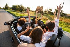 Young girls and guys are sitting in a black cabriolet, holding their hands up and making selfie on a warm sunny day. stock photo
