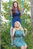 Young girls on handmade swing in summer apple trees garden Royalty Free Stock Photography