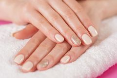 Young girls hands with cream color nails polish on fingers stock photography