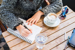 A young girls hands holding a pen and writing on notebook Royalty Free Stock Photography