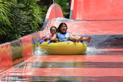 Young Girls Happy on Water Slide royalty free stock images