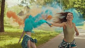 Young girls have fun with colored smoke and jump outdoors in slow motion