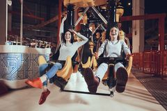 Young girls have fun in the park. Happy friends ride on attractions Royalty Free Stock Image