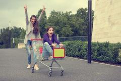 Young girls have fun with the shopping trolley.  Royalty Free Stock Photos