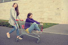 Young girls have fun with the shopping trolley.  Stock Images