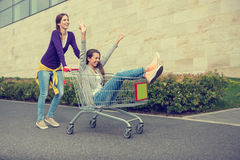 Young girls have fun with the shopping trolley.  Royalty Free Stock Images