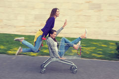 Young girls have fun with the shopping trolley.  Royalty Free Stock Photography