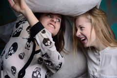 Young girls have fun at studio. With pillows, with cushions Royalty Free Stock Photos