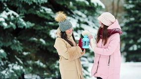 Young girls holding Christmas candlelight outdoors on beautiful winter snow day and warm their hands stock footage