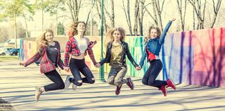 Young girls holding hands and jumping together. Joyful young girls holding hands and jumping together. Four happy teenage girls friends jumping high at the park stock image